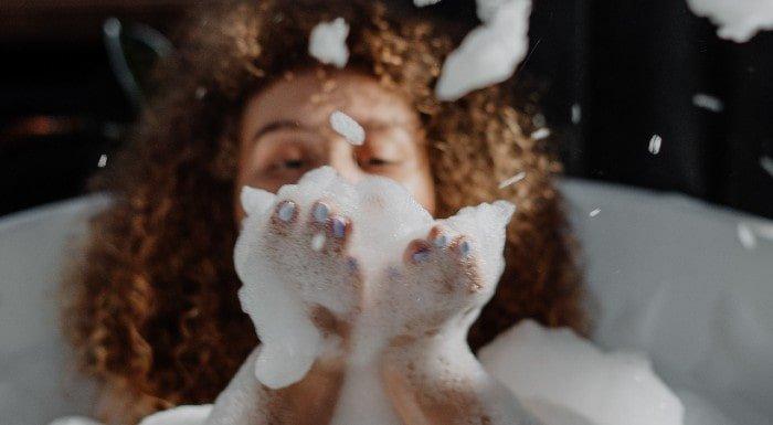 Kobieta zdmuchująca pianę z rąk podczas gorącej kąpieli dla poprawy zdrowia serca.