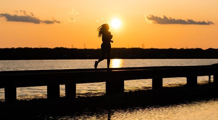 Biegnąca kobieta o zachodzie słońca by utrzymać zdrowie psychiczne
