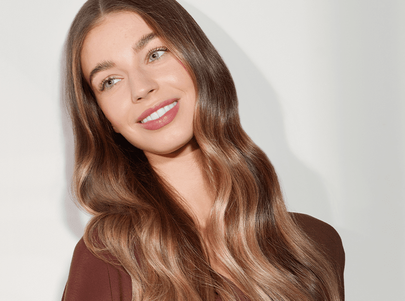 Woman smiling showing the results from using Christophe Robin's luxury hair products. Woman has long, glossy brown hair.