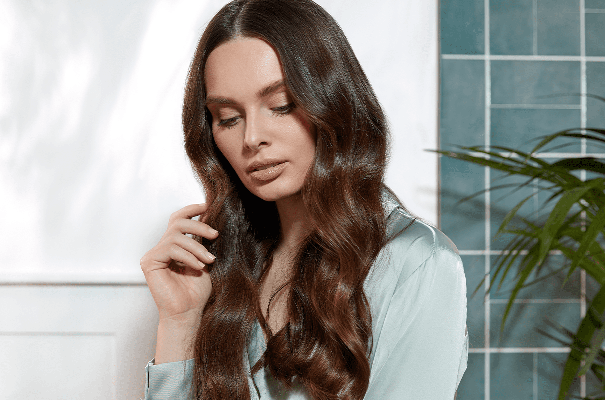 Young brown haired woman with long, glossy strands with her hand touching her hair in the bathroom.