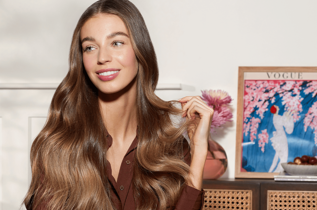 Woman smiling with long, beautiful brown hair. Behind her is a vintage Vogue cover in a frame.