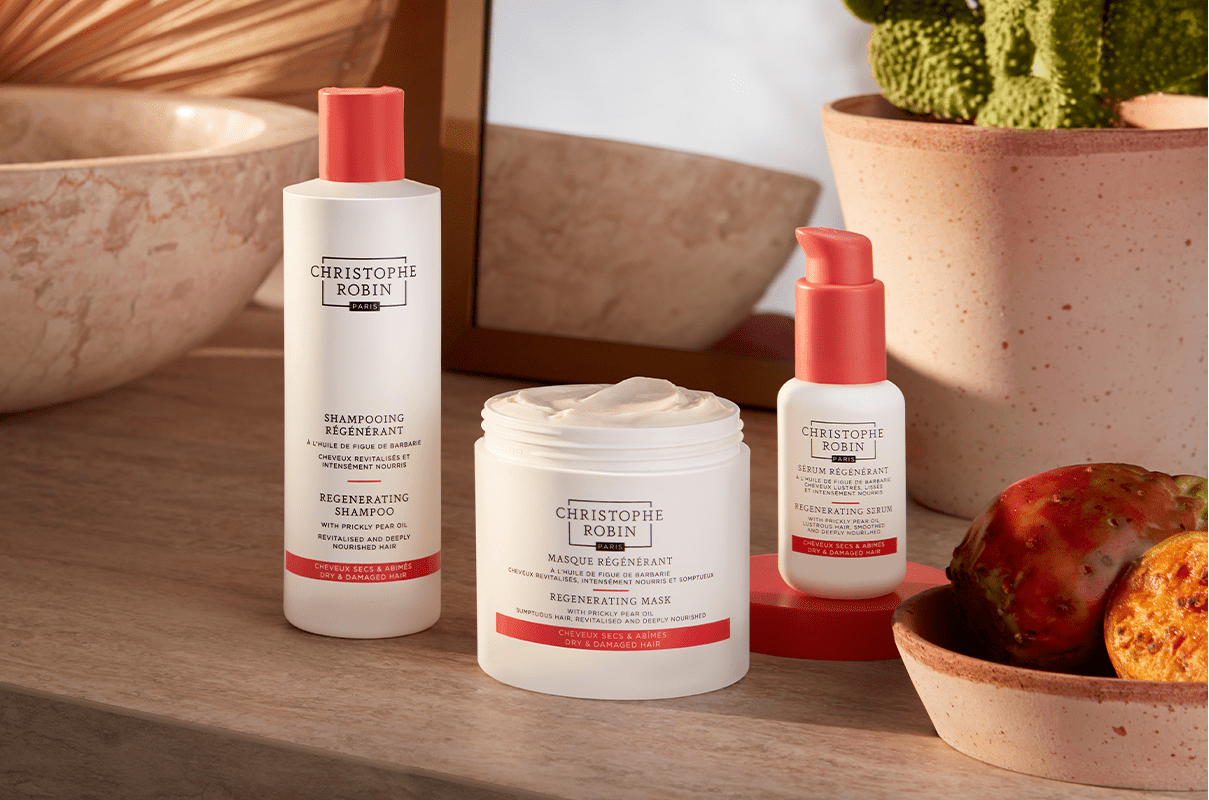 3 luxury hair care products by Christophe Robin's Regeneration range. 3 white bottles with coral accents on the bottles.