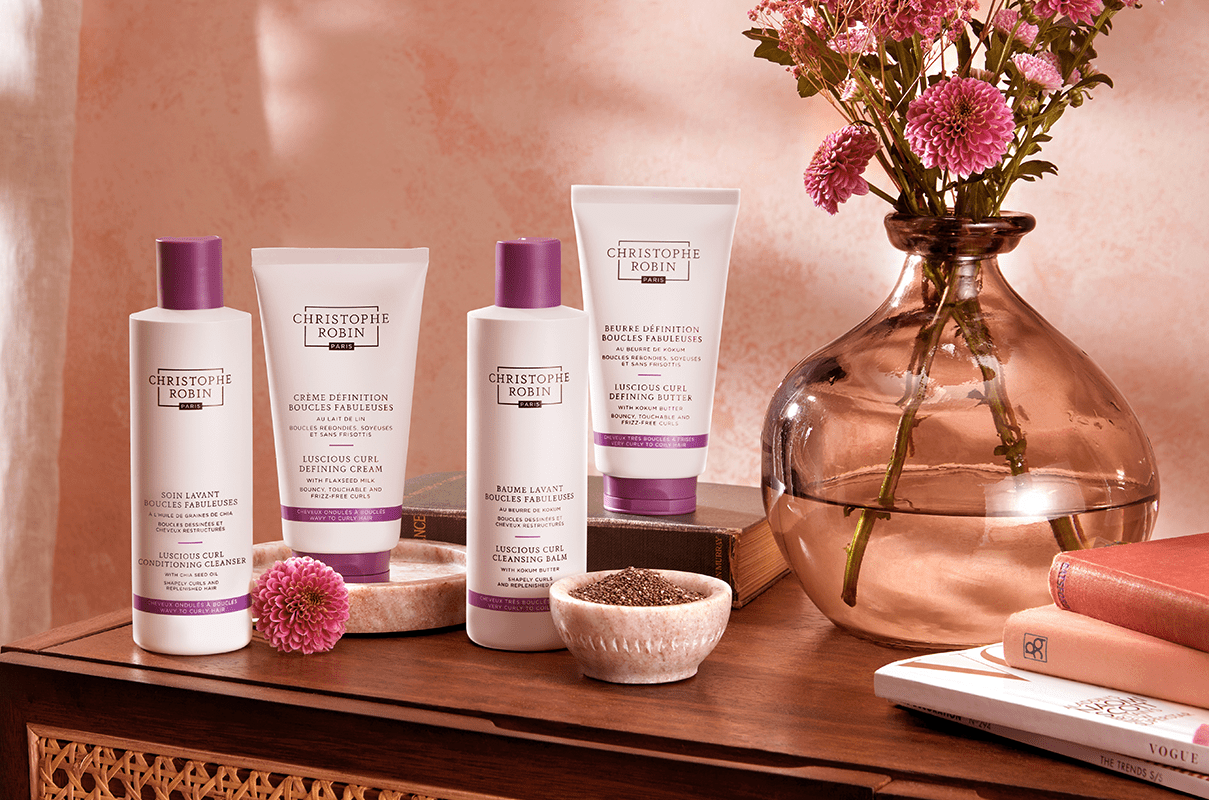 4 of the best hair care products for curly hair by Christophe Robin's Curl Enhance range. 4 white bottles with purple accents.