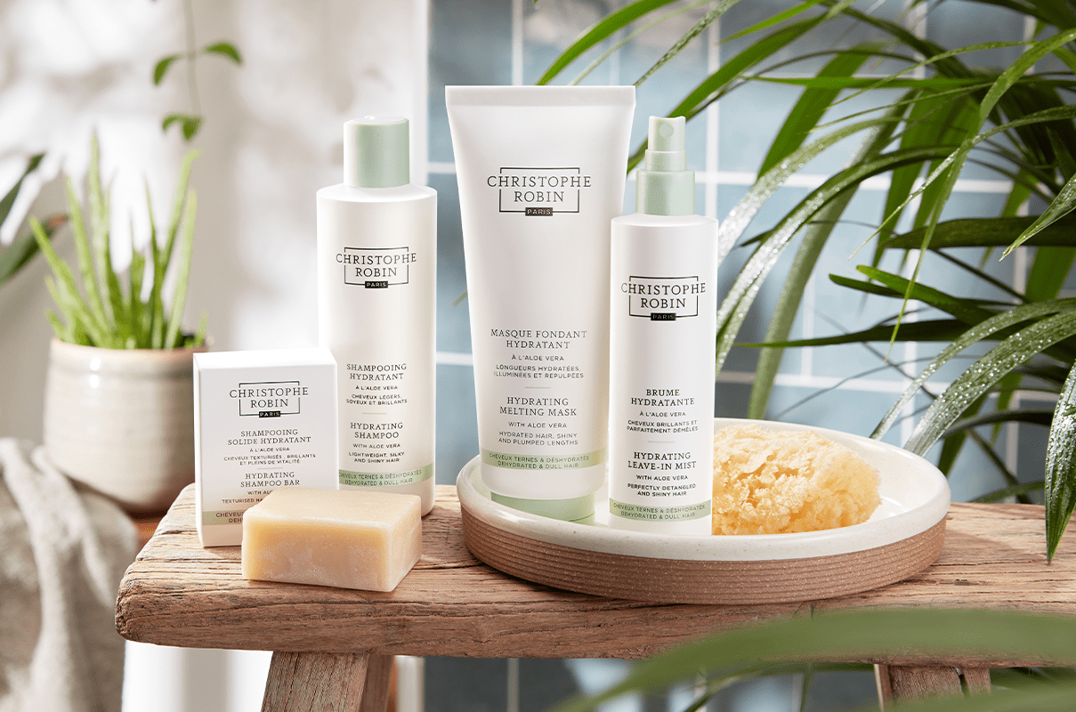 Four professional products by Christophe Robin's Hydrating range. White bottles and a white box with olive green accents.