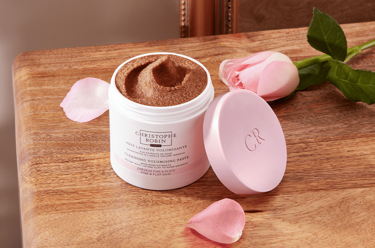 White container of the Cleansing Volumising Paste with Rose Extracts on top of a wooden table with a pink rose next to it.