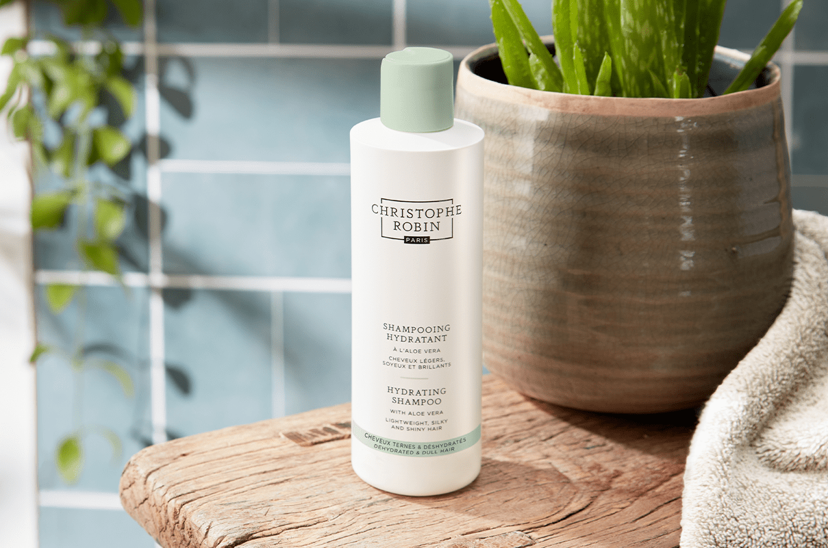 White bottle of the Hydrating Shampoo with Aloe Vera in a bathroom next to a plant on a wooden table.