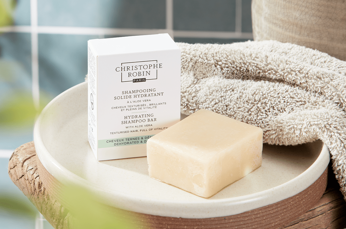 White box of Hydrating Shampoo Bar with Aloe Vera in a bathroom next to a beige towel on top of a wooden stool.