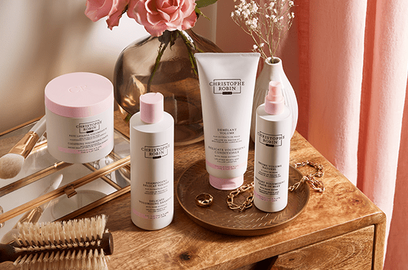 Four sustainable hair products by Christophe Robin's Volume range. Four white bottles with baby pink accents.