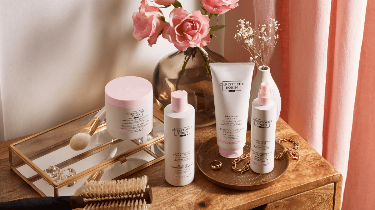 Christophe Robin pink and white Volume hair products on a dressing table with flowers