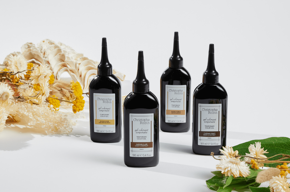 Four luxury products by Christophe Robin's temporary colour gel range. Black bottles with colours shown on bottles.