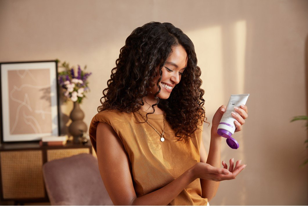 Woman with dark brown Z shaped curls using Christophe Robin's curly hair balm.