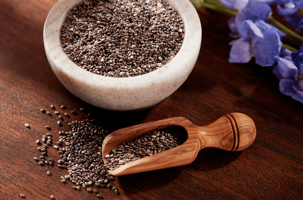 Chia seed oil for hair on a wooden table in a mortar bowl next to purple flowers.