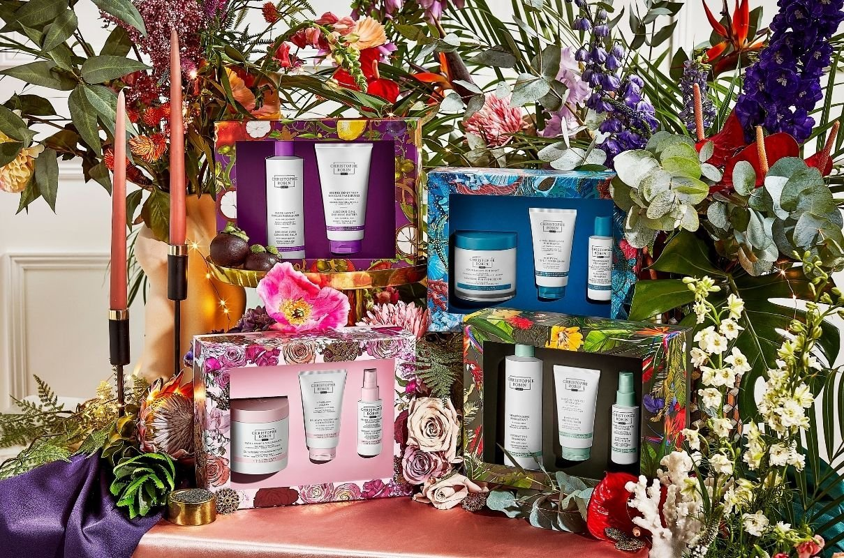 Four different Christophe Robin hair product Christmas gifts in front of a huge colour display of flowers