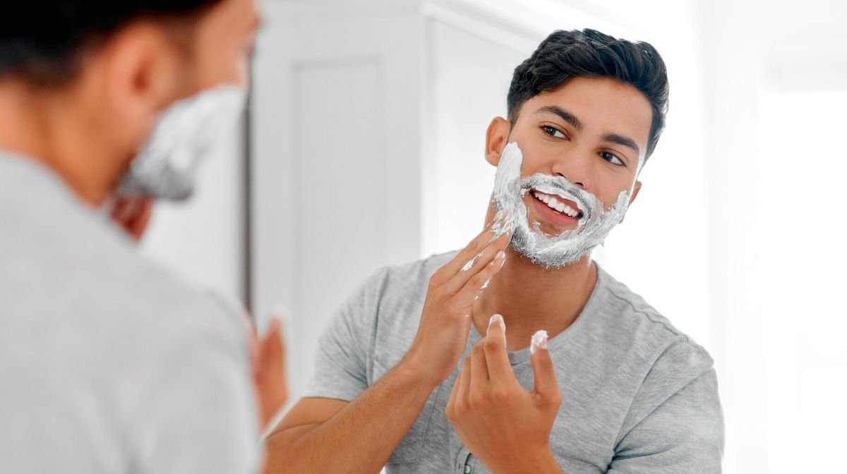 man applying shaving cream to soften coarse beard hair