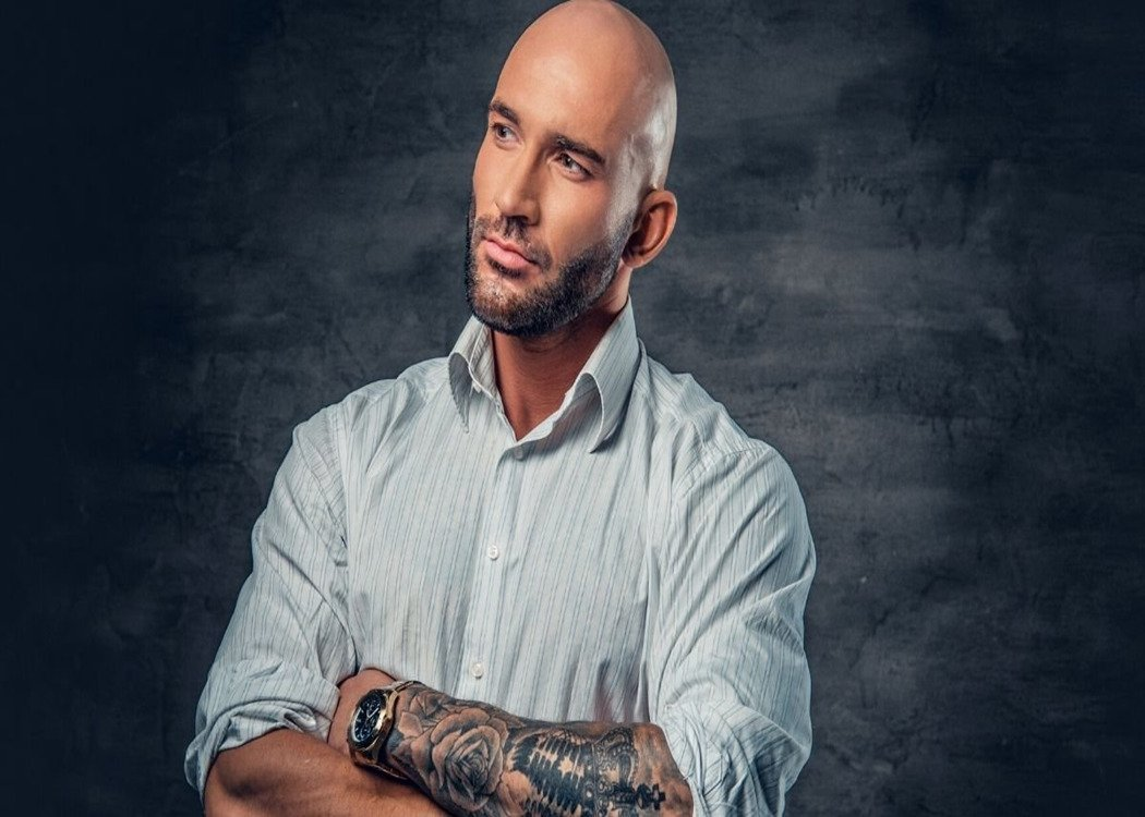 smartly dressed man with tattoos and a shaved head