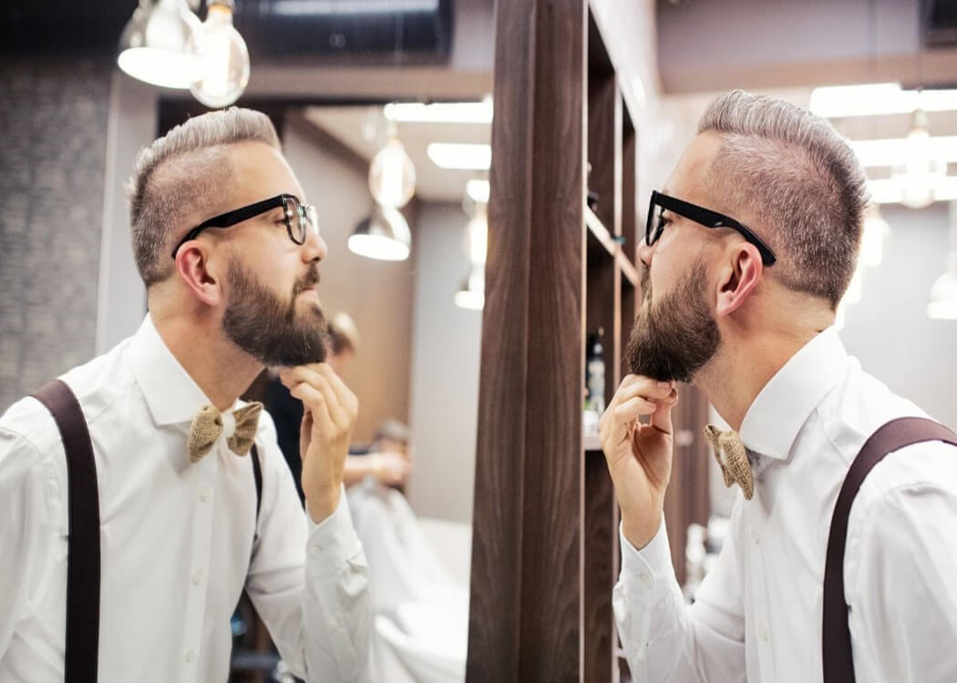 man with hipster beard looking in the mirror to check for beard growth