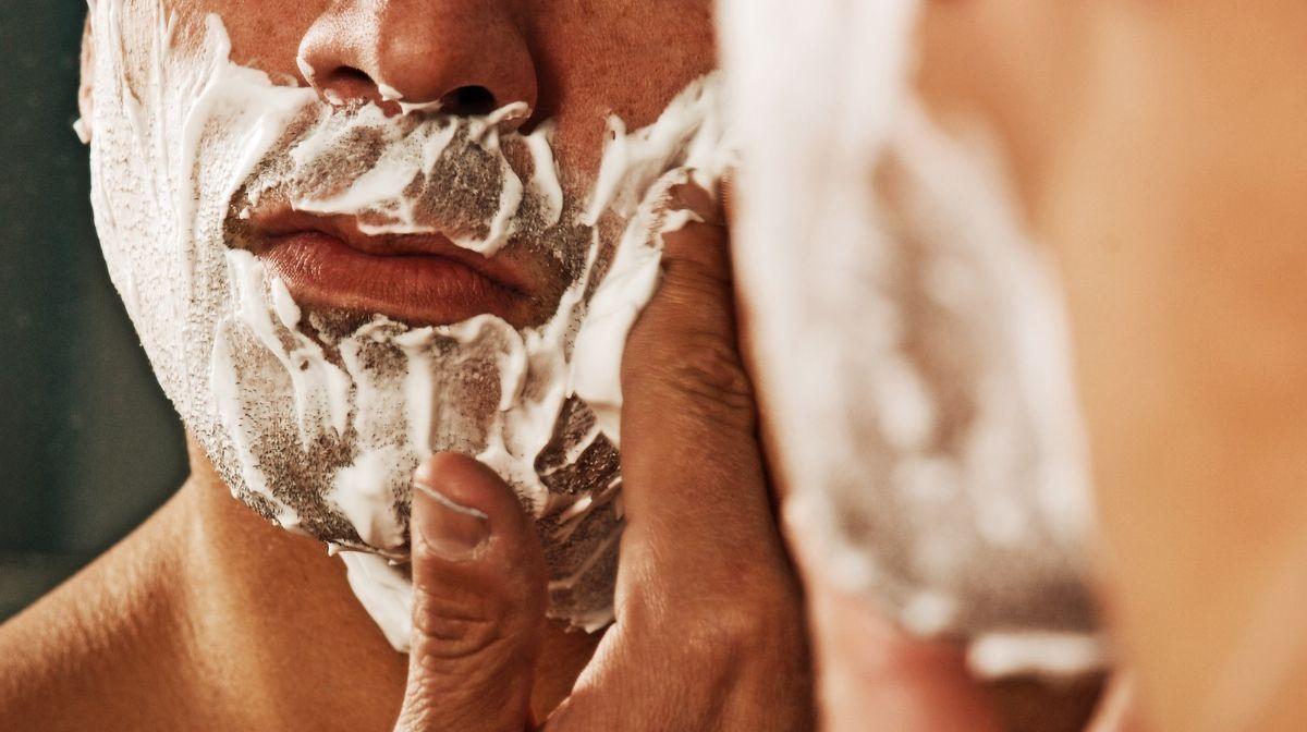 man using shaving cream to prevent dry skin after shaving