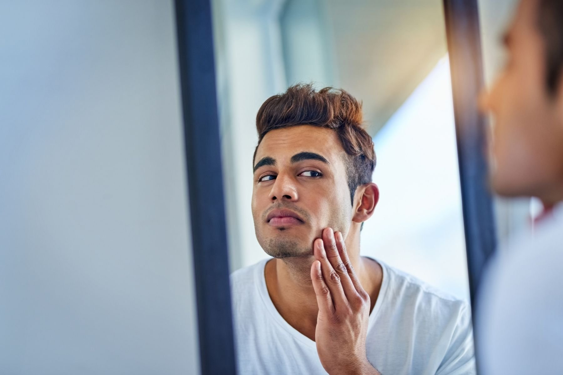 man looking for dry skin in the bathroom mirror before shaving