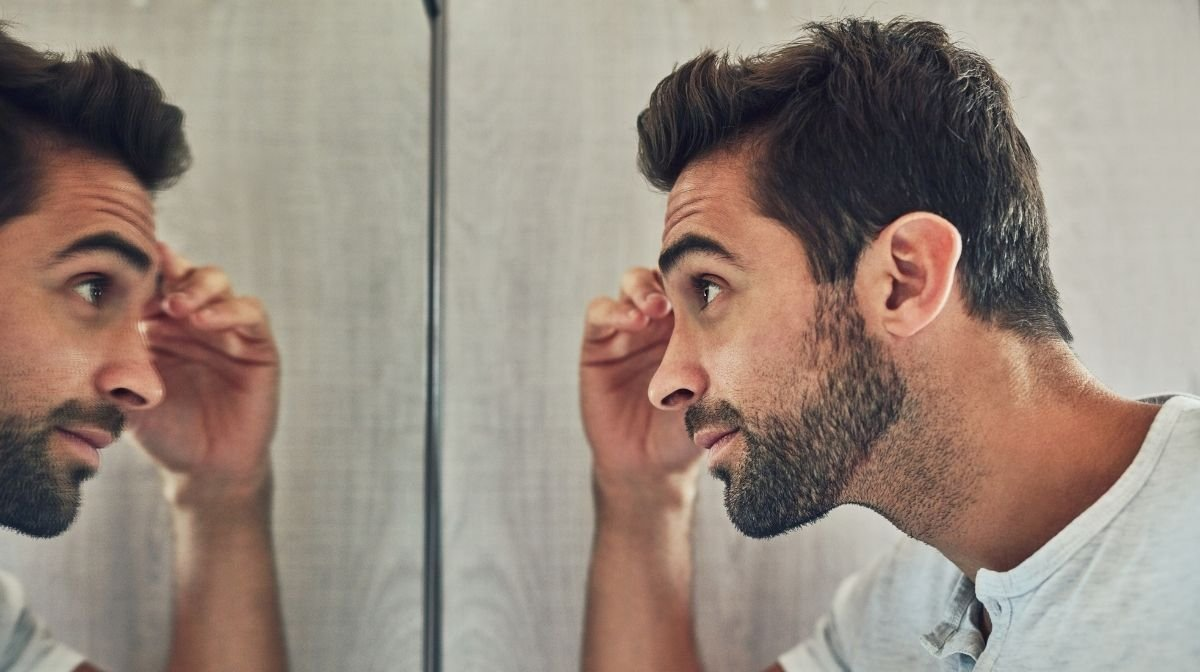 man styling his beard in the mirror