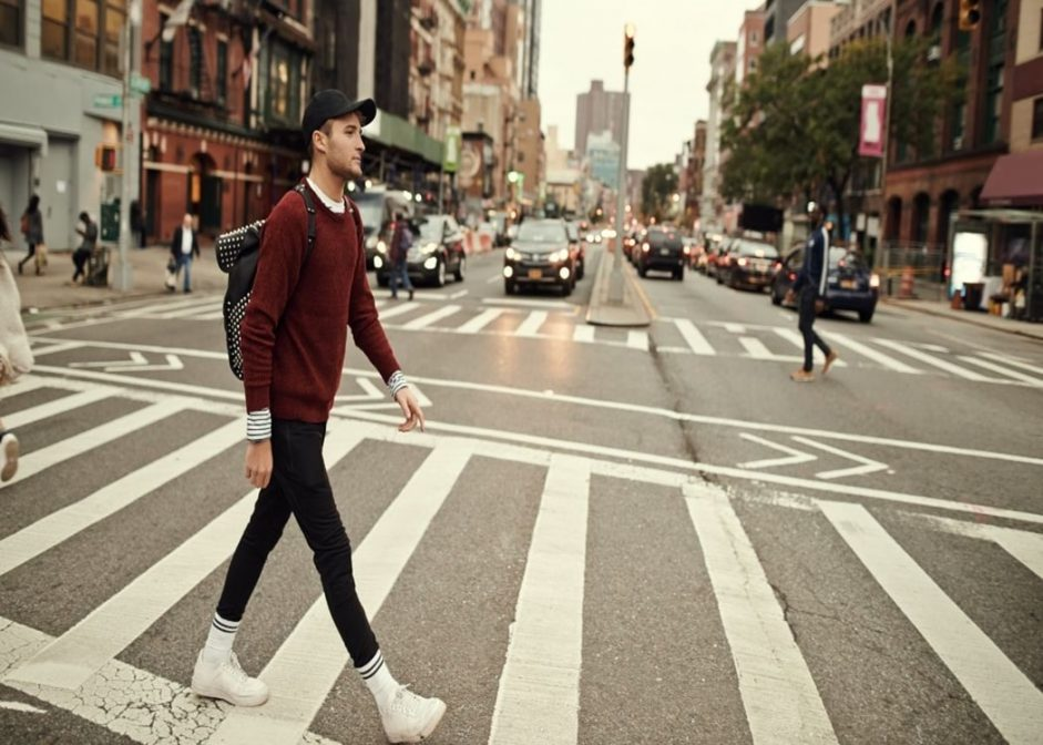 man crossing the road wearing a jumper over a t-shirt
