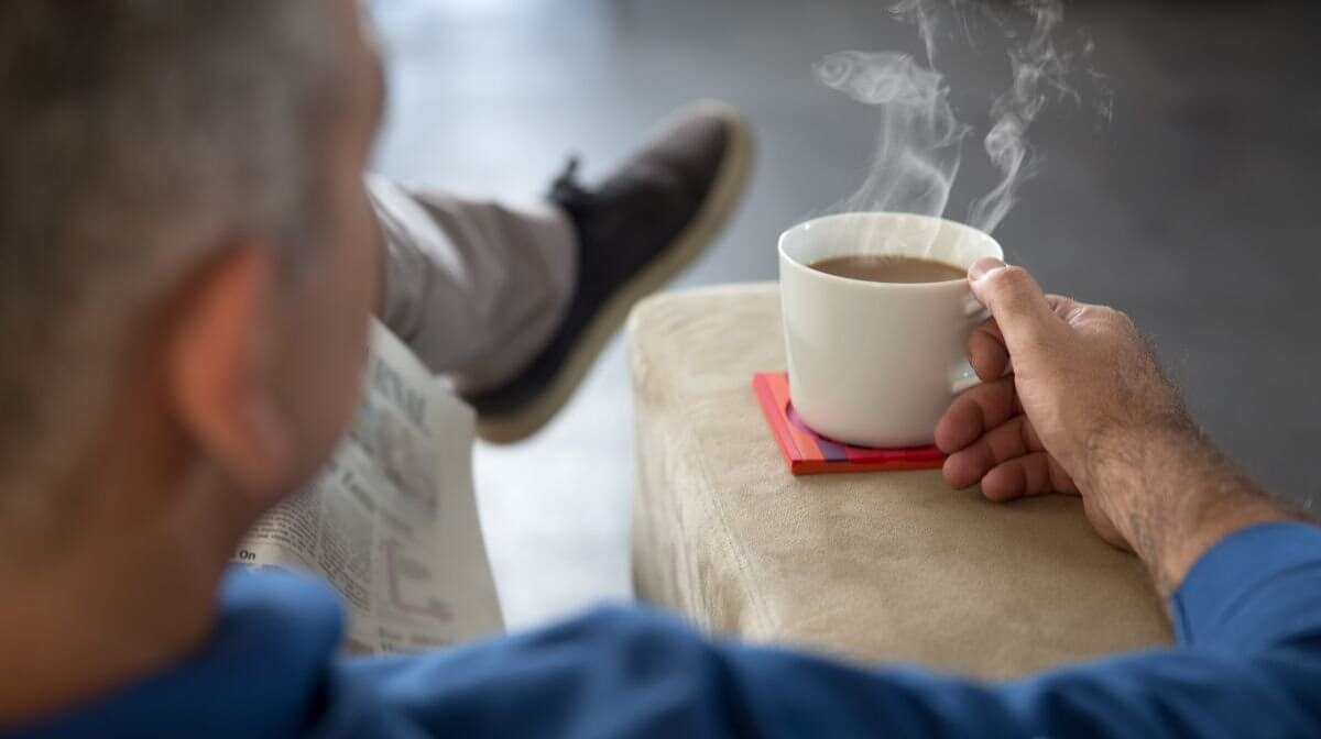 man enjoying time to himself with a cup of tea and the newspaper