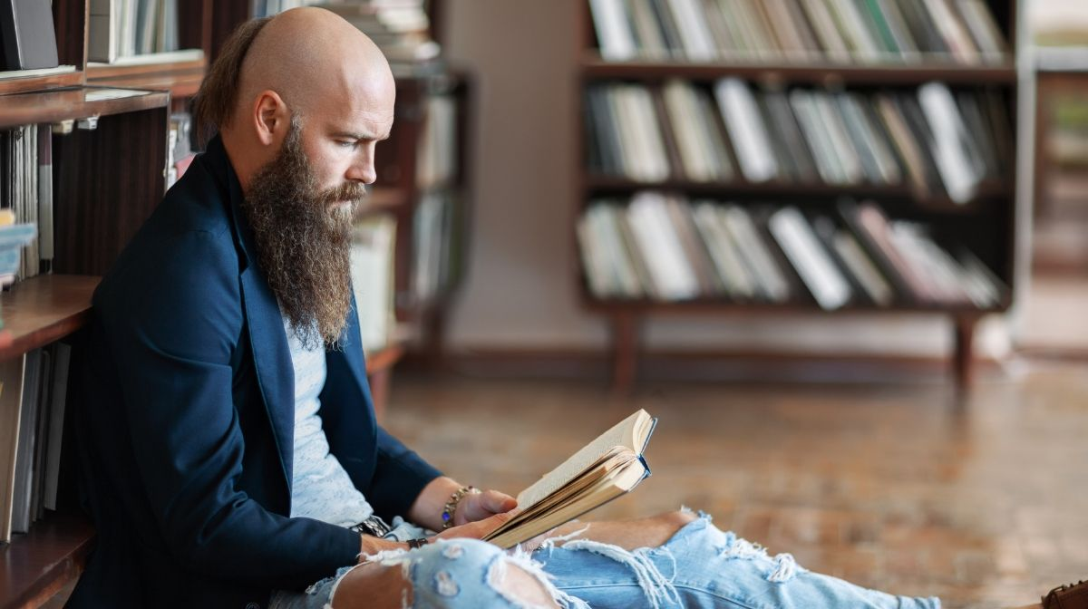 man with a full beard and bald head to take attention away from his receding hairline