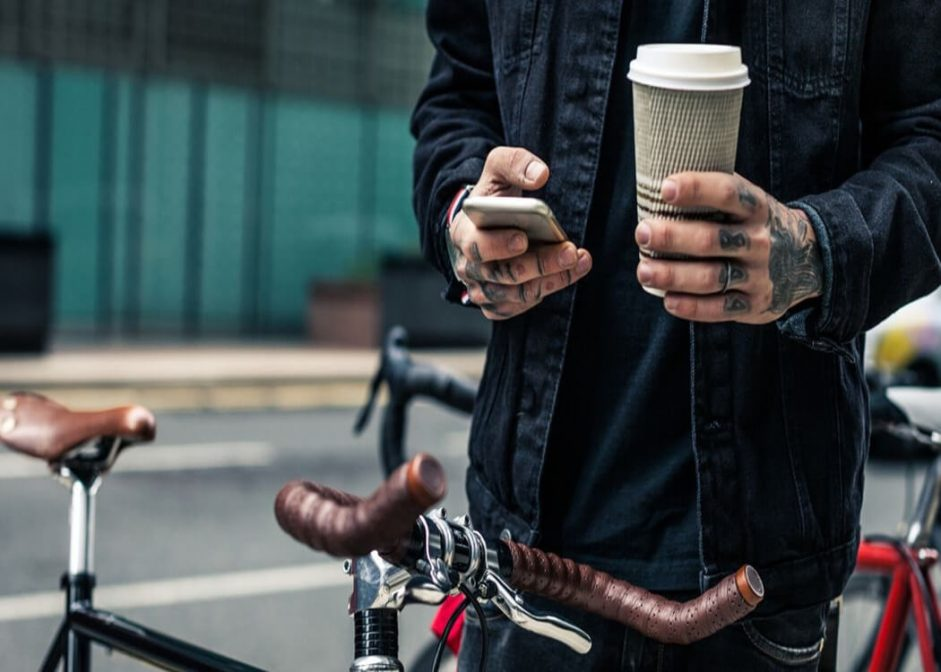 man cycling while using a recycled coffee cup as part of a green lifestyle