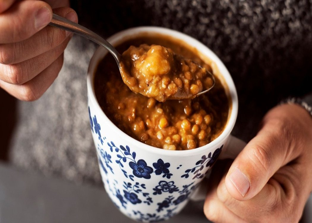 man eating homemade soup out of a mug