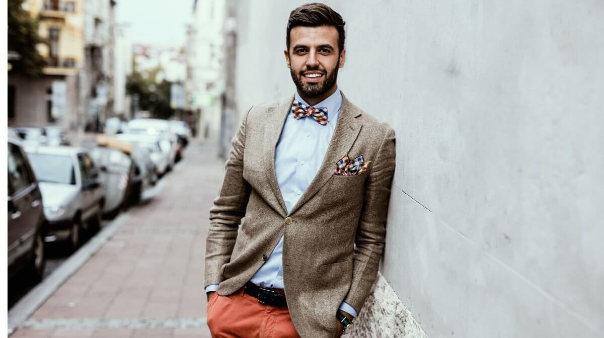 man looking stylish in orange trousers, a smart blazer and quirky bow tie