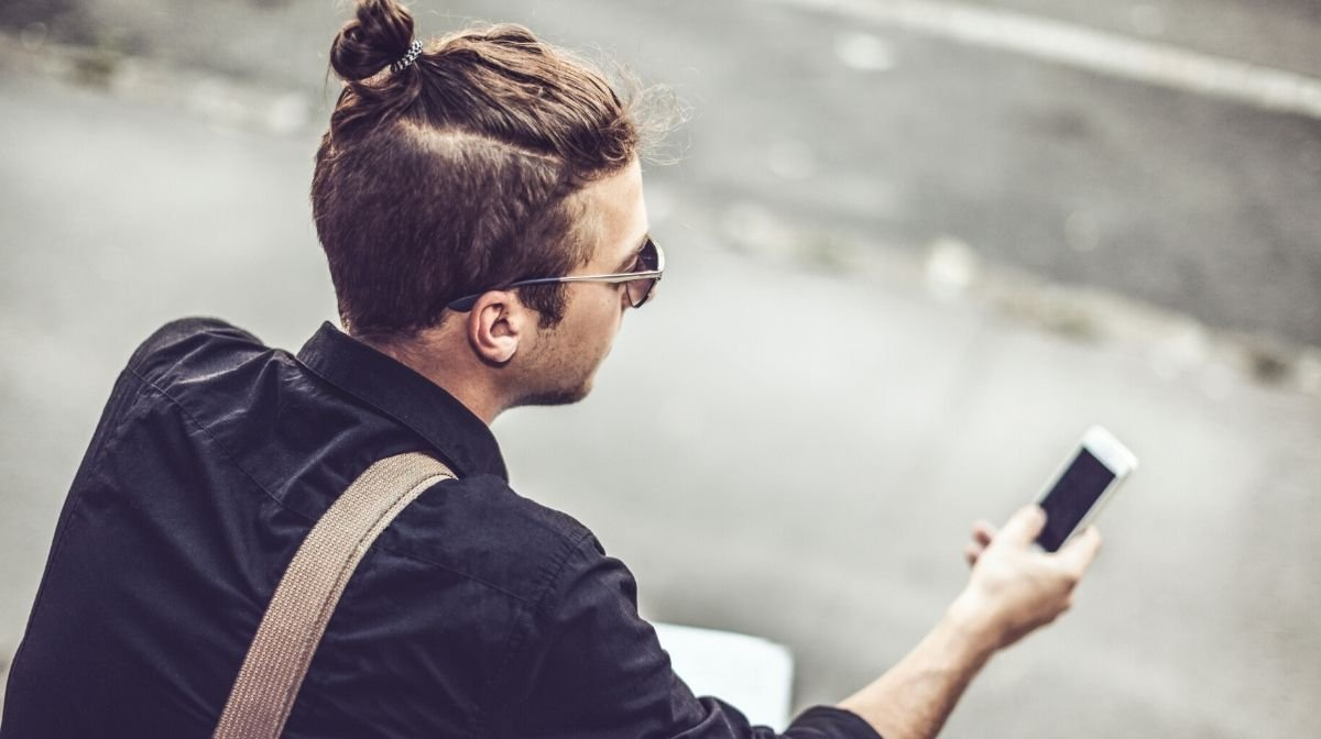 man with a man bun hairstyle as he grows out his undercut