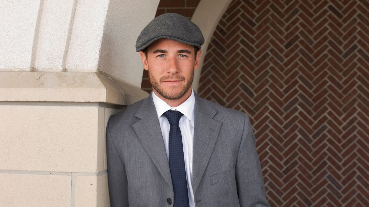 man wearing a flat cap and long coat in the style of the Peaky Blinders
