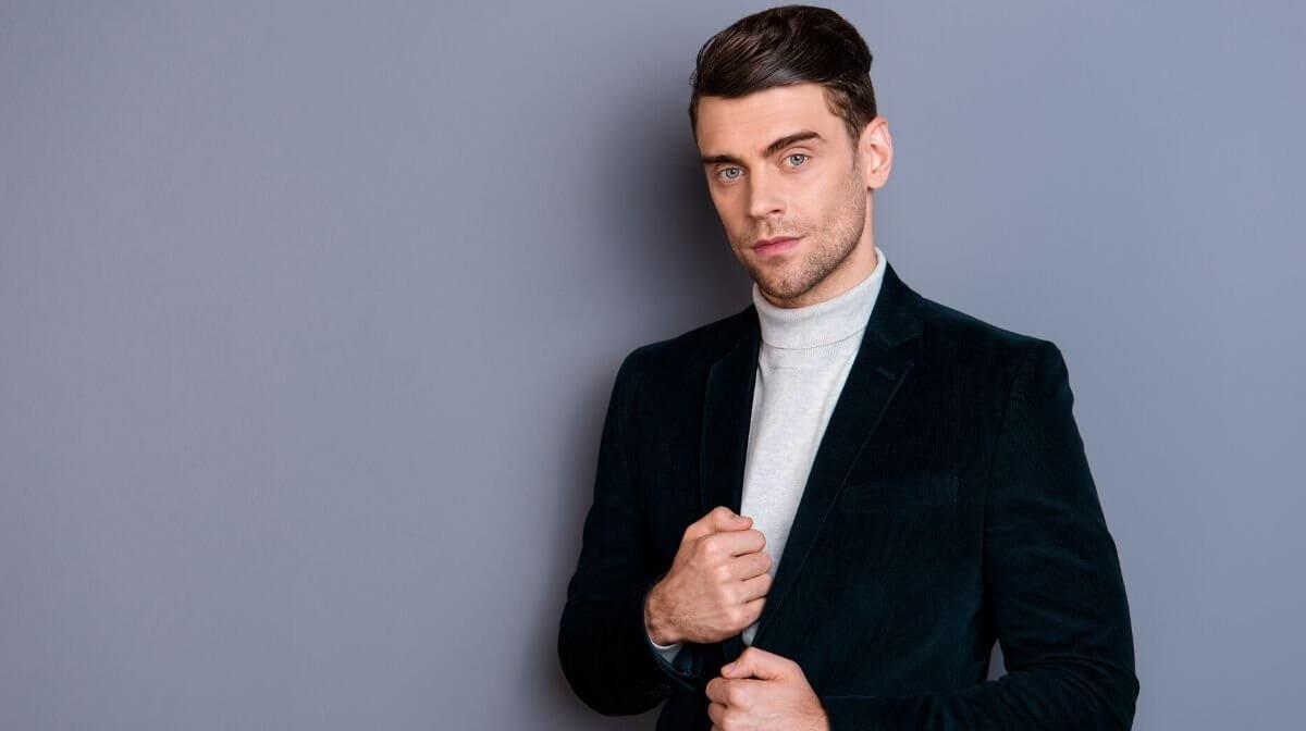 man wearing a roll neck jumper underneath a velvet blazer