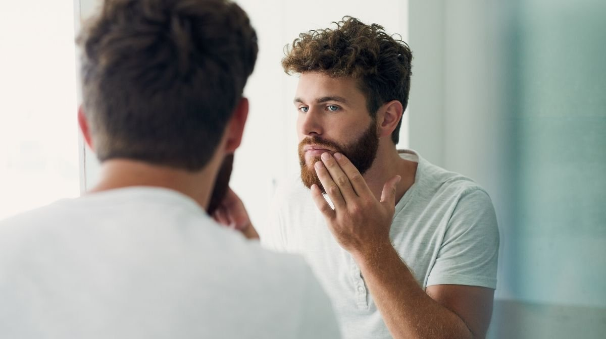 man exfoliating the skin around his beard