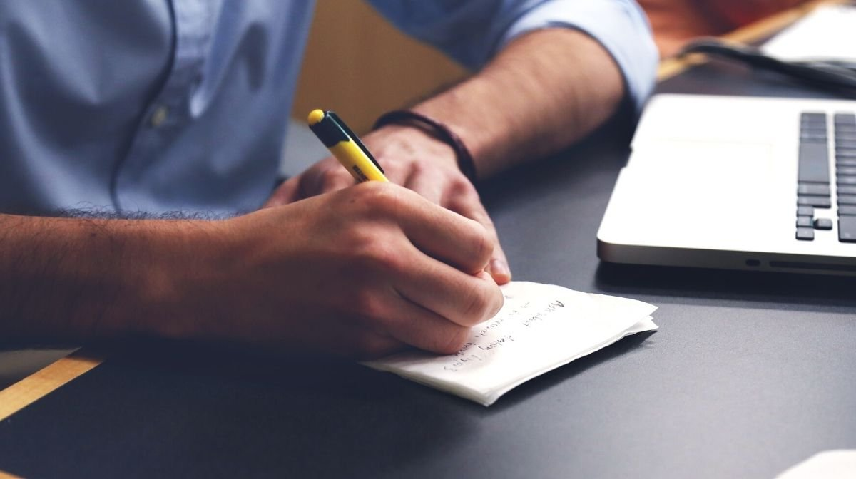 man writing a to-do list to keep him on track