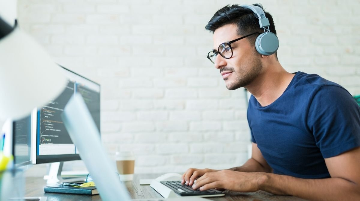 man using headphones to maintain focus while working from home