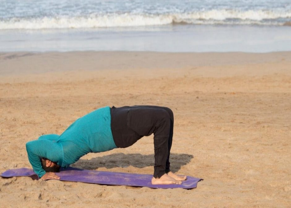 man in the half-bridge yoga pose at the beach