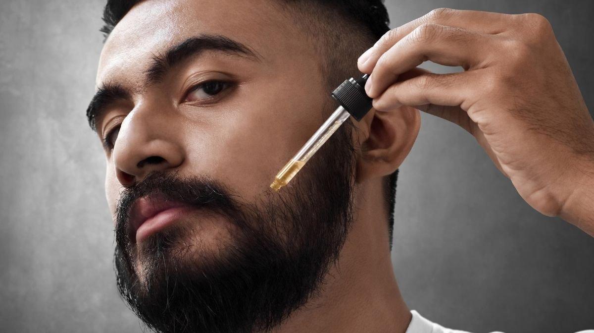 man applying fragrance to his beard