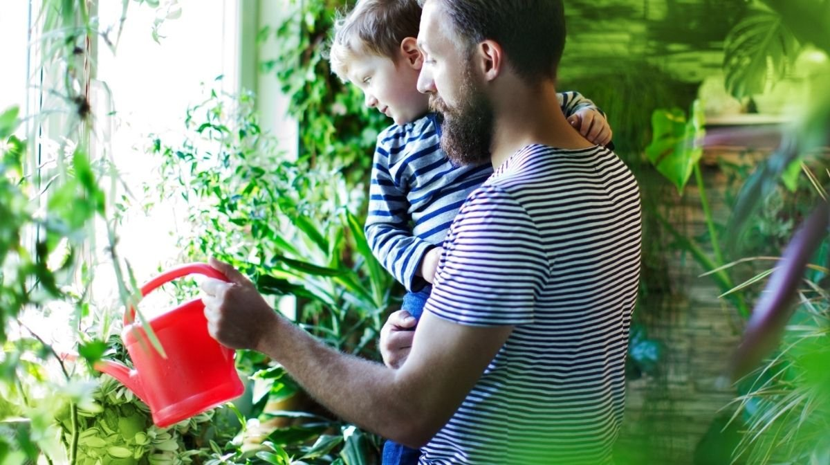 man watering plants with his young son