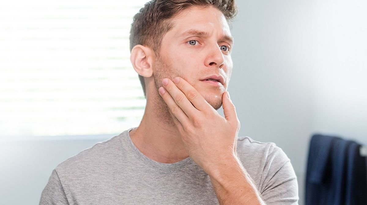 man inspecting his clean face in the mirror