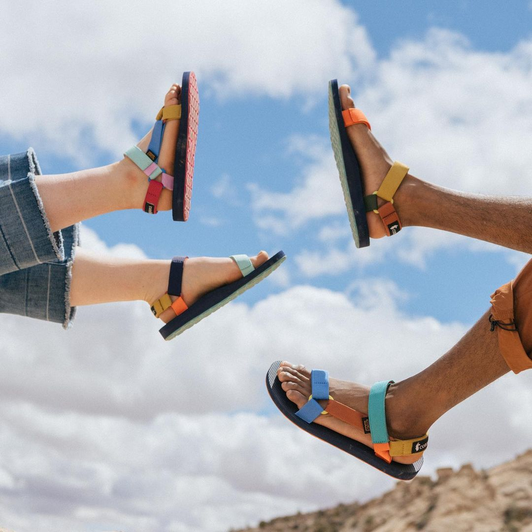 Two people lifting there feet wearing sandals