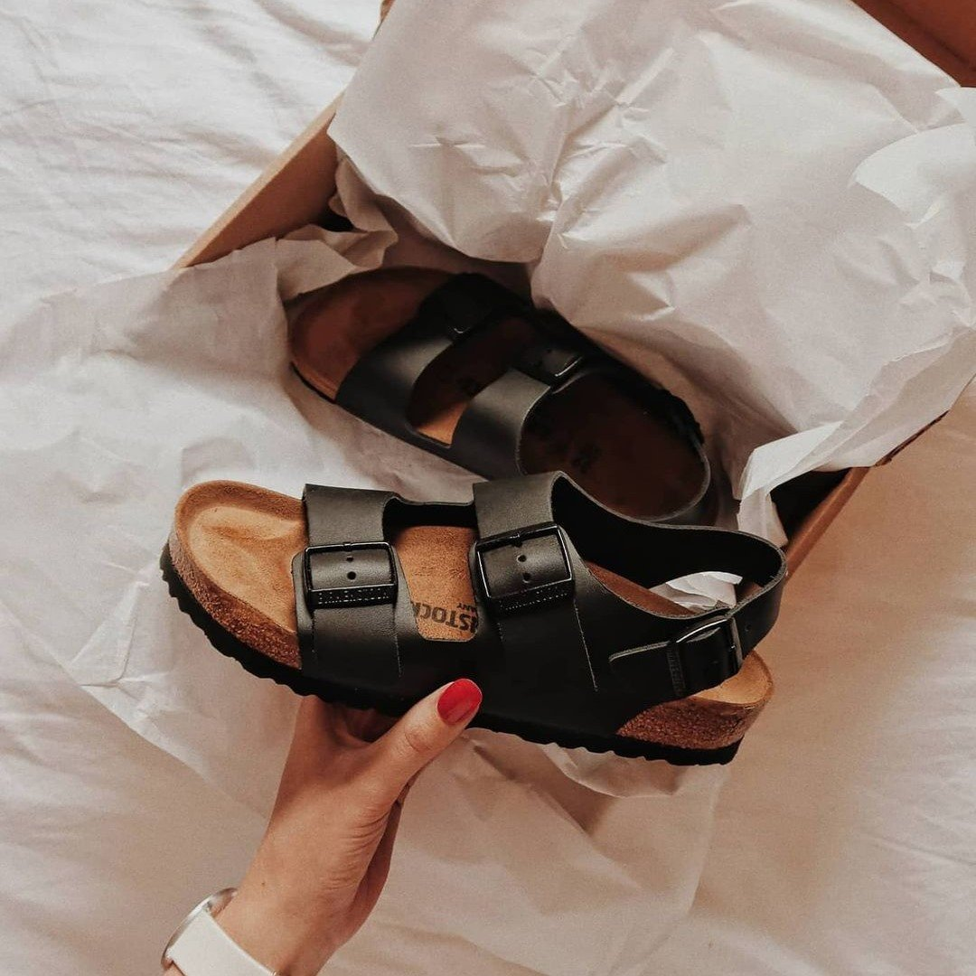 woman holding birkenstock sandal