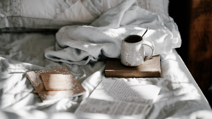 book and mug on bed