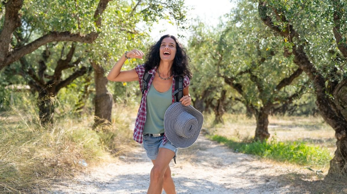 woman walking among olive trees in the sun