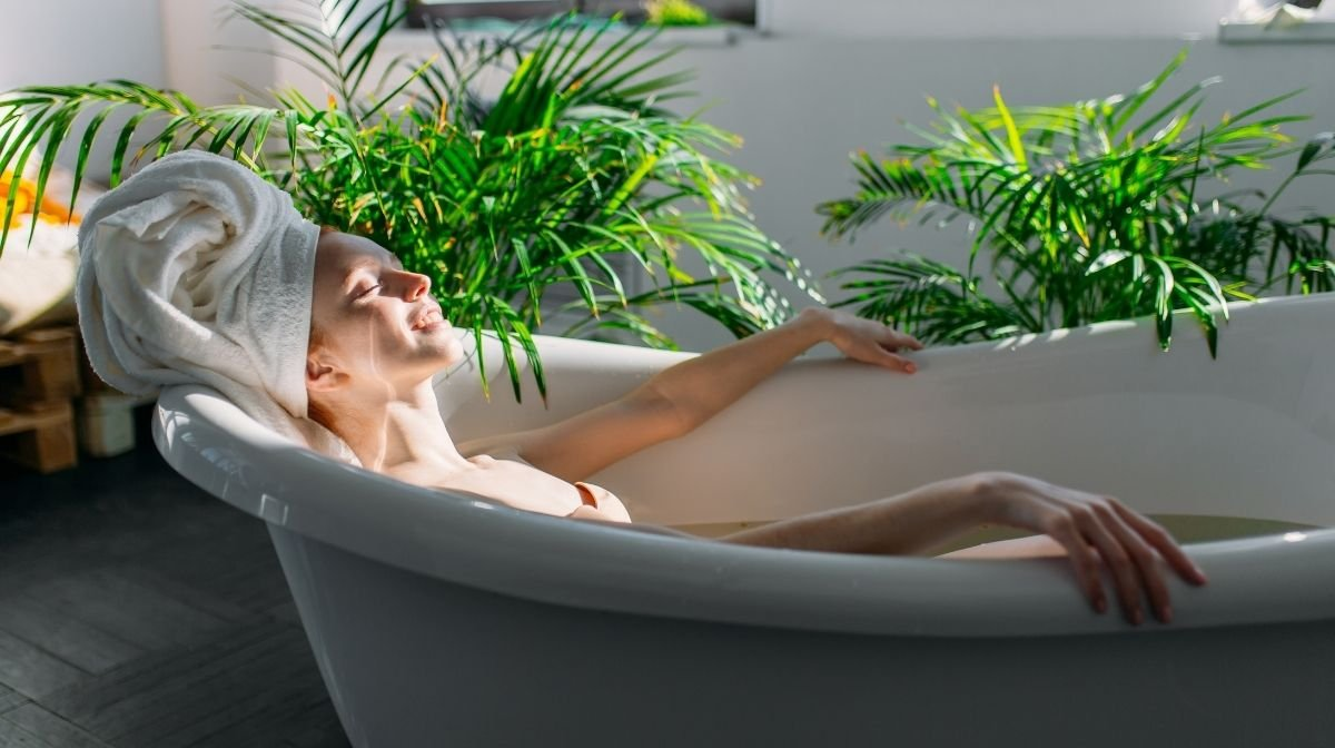 woman relaxing in bath surrounded by plants