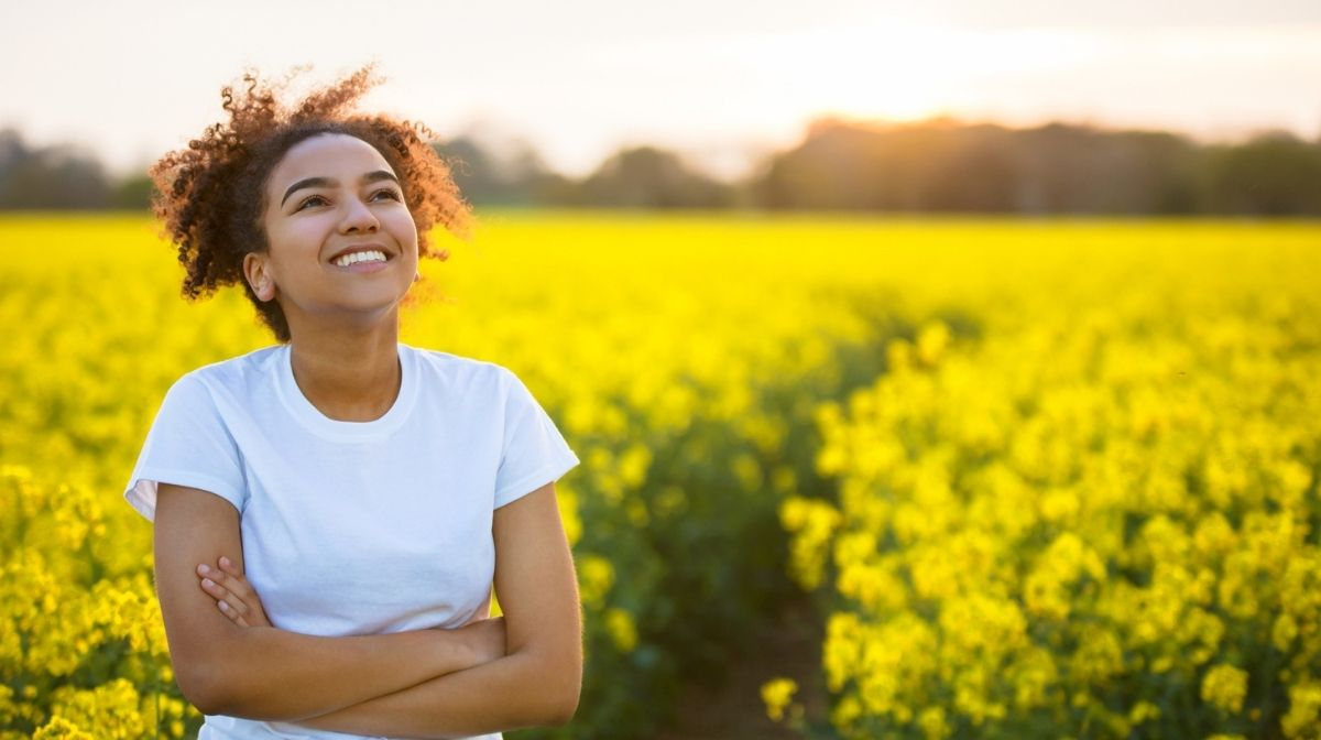 woman relaxing in a field of yellow flowers