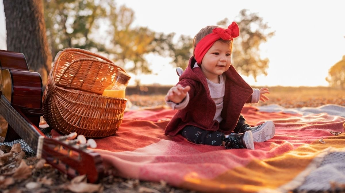 baby sitting on a picnic blanket outdoors