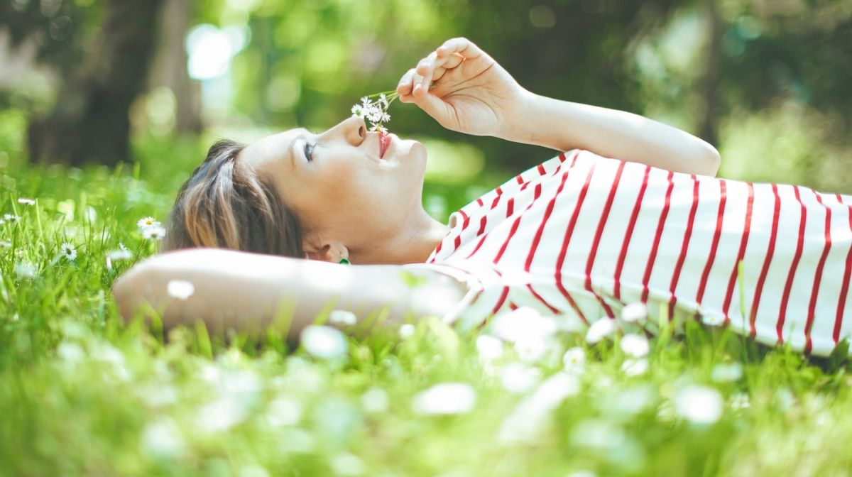 woman lying in grass, smelling flowers