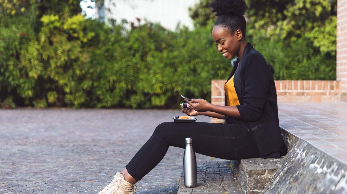 woman with water bottle checking her phone