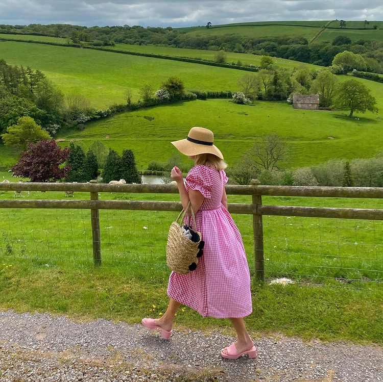 Women in a pink dress walking in the countryside