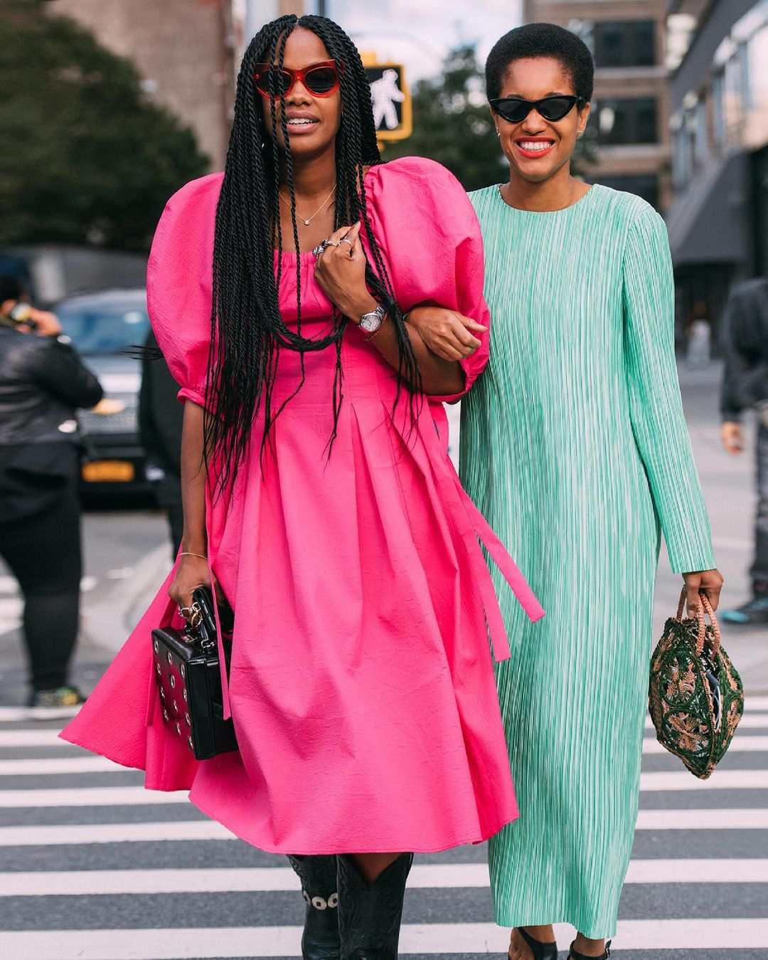Two women crossing the street in brightly coloured dresses